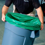 Photo of large garbage can with green liner.